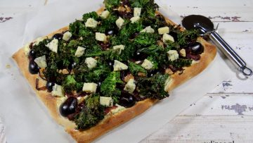 Pizza met rode ui, boerenkool, druiven en blauwe kaas