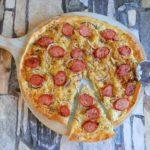 Pizza met zuurkool, rode ui en rookworst