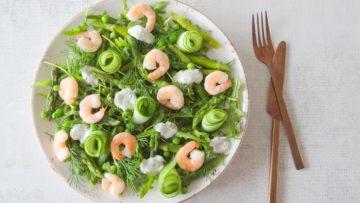 Groene voorjaarssalade van rucola, groene asperges, garnalen en dille